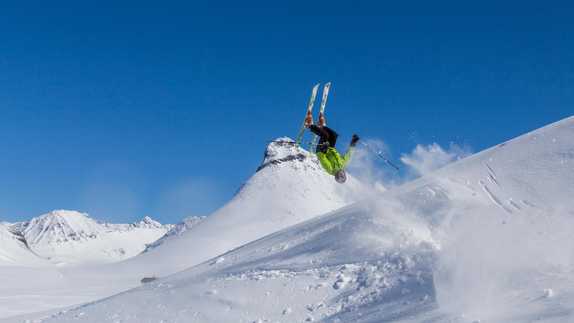 Person auf Skiern macht einen Salto